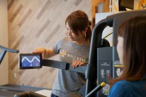 ウェルベース矢巾のウェルネスシステムでのトレーニングサポートを説明するトレーナー